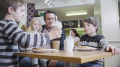 2 cute little boys in a cafe enjoy sharing their milkshakes - stock footage