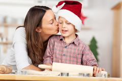 woman kissing son while baking for christmas - stock photo