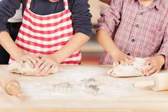 brothers kneading cookie dough at kitchen counter - stock photo