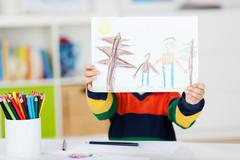 boy displaying drawing at table - stock photo