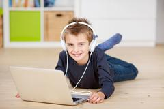 Boy listening music from laptop through headphones Stock Photos
