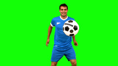 Handsome man juggling a football on green screen Stock Footage