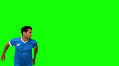 Attractive man heading a football on green screen Stock Footage