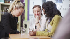 Attractive female friends enjoy a chat and a gossip over drinks Stock Footage