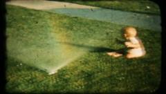 98 - baby plays in frontyard sprinkler - vintage film home movie Stock Footage