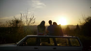 Teens Watching Sunset On Top Of Car Stock Footage