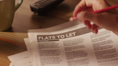 Stock Video Footage of Man Marking Advertisement of Flats in a Newspaper Using Red Pencil 4K