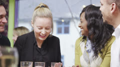Happy group of friends or business colleagues chat together in a small cafe - stock footage