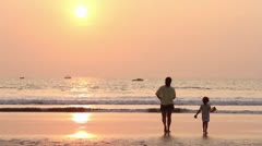 Mom and daughter on the beach, sunset. - stock footage