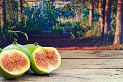 fresh figs on rustic wooden table against forest background - stock photo