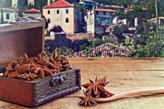 Star anise spice on rustic wooden table with old countryside village in the b Stock Photos