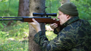 Stock Video Footage of Man with optical rifle and binoculars in the woods episode 3