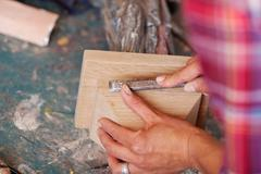 woman carving wood in workshop - stock photo