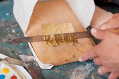 woman's hand cutting golden paper with knife on board - stock photo