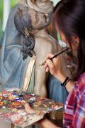 Woman painting jesus christ's statue with paintbrush Stock Photos