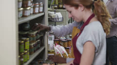 Customers and staff members in a small friendly delicatessen or food store - stock footage