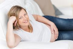 Pregnant woman with hand on tummy lying on sofa Stock Photos