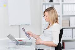 pregnant businesswoman looking at ultrasound scan reports at desk - stock photo