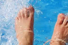 refreshing the feet in the pool - stock photo