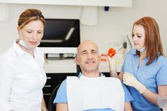 dentists examining patients mouth - stock photo