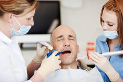 dentists using dental tools - stock photo