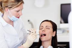 dentist examining female patients mouth in clinic - stock photo