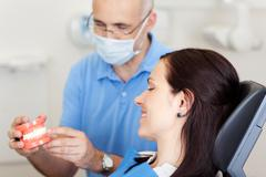 male dentist explaining artificial teeth - stock photo