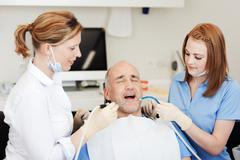 dentists examining patients mouth with tools - stock photo