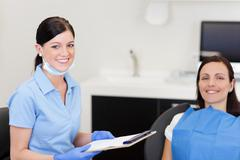 Stock Photo of young smiling dentist assistant and patient