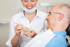 smiling female dentist explaining artificial teeth - stock photo