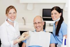 dentist with teeth model and male patient - stock photo