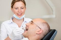 female dentist examining male patients mouth - stock photo