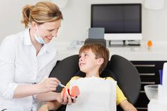 Dentist explaining brushing procedure to little boy in clinic Stock Photos
