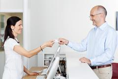 Receptionist receiving card from patient in dentist clinic Stock Photos