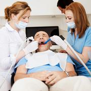 Dentists examining man's mouth in clinic Stock Photos