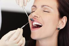 Female patient receiving treatment from dentist Stock Photos