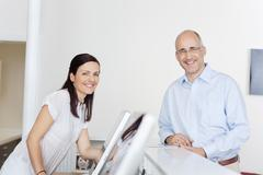 Happy patient and receptionist at reception in dentist's clinic Stock Photos