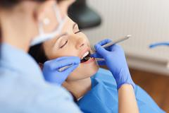 Dentist examining mid adult patient's mouth in clinic Stock Photos