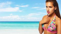 Young beautiful woman enjoying the sun on the beach Stock Photos