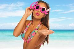 Young beautiful woman enjoying the sun on the beach wearing cool glasses Stock Photos
