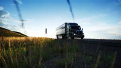 Eighteen Wheeler truck drives at sunset. Dolly shot.  - stock footage