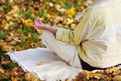 Senior Woman Meditating In Lotus Position At Park Stock Photos