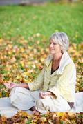 Woman Meditating In Lotus Position Stock Photos