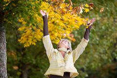 Autumn Leaves Falling On Happy Senior Woman - stock photo