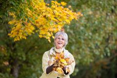 Senior Woman Holding Autumn Leaves Stock Photos