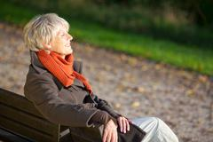 Senior woman enjoying sunlight on park bench Stock Photos