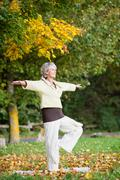 woman standing on one leg while doing yoga in park - stock photo