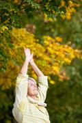 senior woman doing stretching exercise in park - stock photo