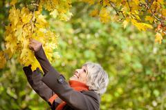 senior woman holding tree branch - stock photo