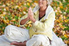 woman with hands clasped meditating in park - stock photo